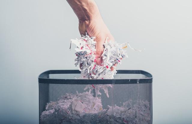 foto de mão jogando papel triturado no lixo
