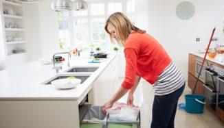 foto de mulher mexendo no lixo doméstico