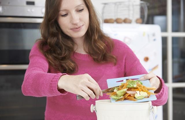 foto de mulher jogando restos de alimentos no balde