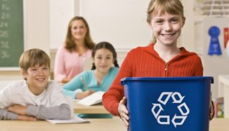 foto de criança segundo lixo com símbolo de reciclagem